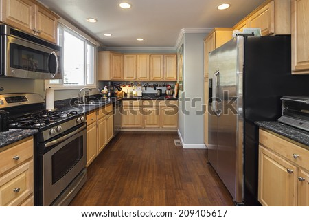 Luxury modern styled kitchen with light wooden cabinets, stainless steel appliances, ornamented black granite counter. - stock photo