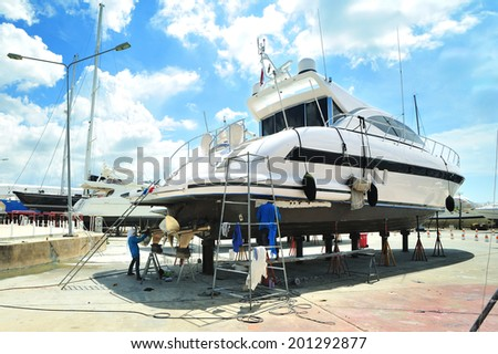 Luxury motor yacht beached at a dock for painting and repair - stock photo