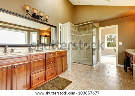Luxury new large bathroom interior with brown tiles and wood cabinets. - stock photo