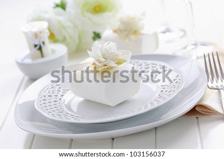 Luxury place setting in white with small present for the guests - stock photo