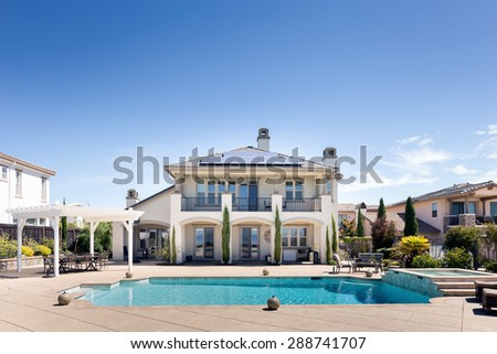 Luxury Pool in front of private mansion with solar panels. - stock photo