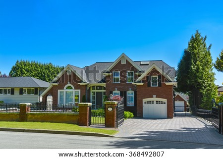 Luxury residential house on sunny day in suburban of Vancouver. Brick house with garage and grid fence in front on blue sky background  - stock photo