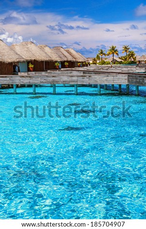 Luxury resort in Maldives, little wooden bungalows over blue transparent water, spending summer vacation on Indian ocean - stock photo
