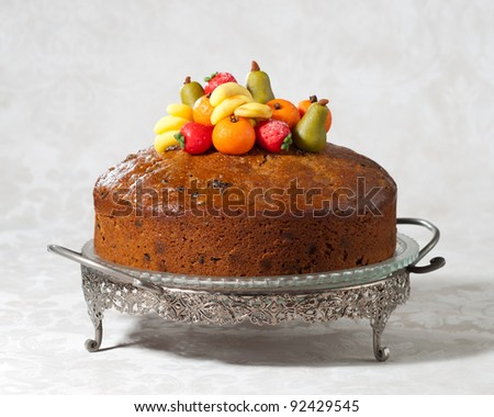Luxury rich fruit cake on cakestand decorated with traditional marzipan fruits - stock photo