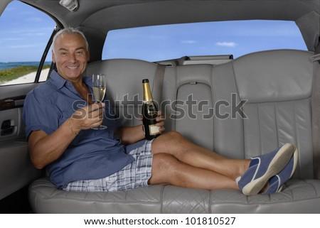 Luxury senior inside a car drinking champagne.Senior inside a limousine enjoying a champagne. - stock photo