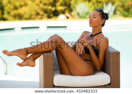 luxury sexy young woman in bikini with many accessories, chains, and jewelry is posing near the swimming pool.  - stock photo