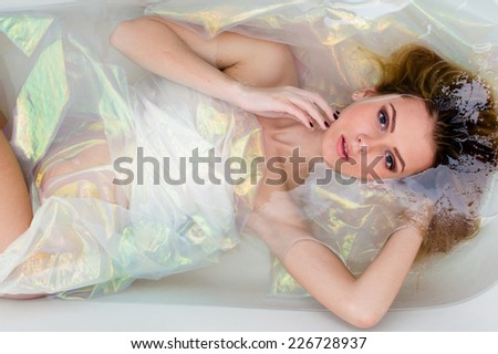 luxury silk spa: portrait of beautiful blonde sexy young woman with red lips relaxing laying in a bathtub water with shining background & looking at the camera  - stock photo