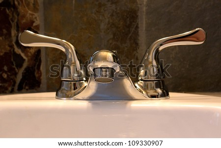 Luxury silver tone bathroom faucet fixture on sink - stock photo