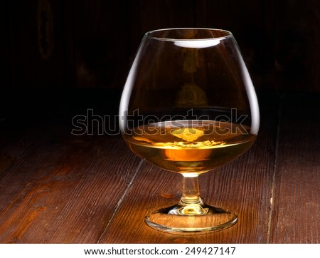 Luxury still life with glass of cognac, on a wood background. Front view with copyspace. Close up shot - stock photo