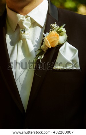 luxury stylish groom with boutonniere on elegant suit and  tie close-up at wedding ceremony - stock photo