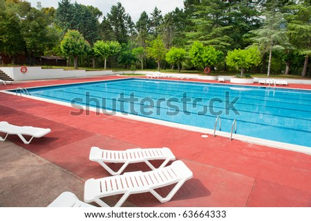 Luxury swimming pool with white resting beds - stock photo