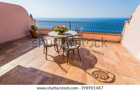 Luxury terrace balcony of exclusive seaside resort with fancy table and chairs fuit and flower bawl and full sea panorama in the beautiful morning lights, Sicily, Italy - stock photo