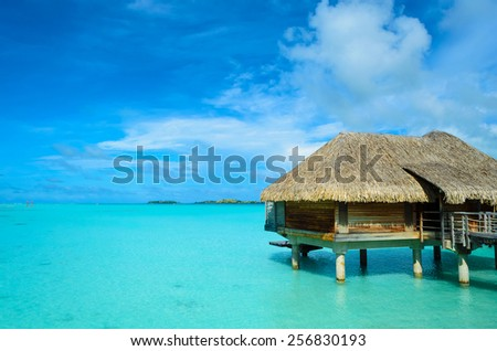Luxury thatched roof honeymoon bungalow in a vacation resort in the blue lagoon of the Pacific island of Bora Bora, near Tahiti, in French Polynesia. - stock photo