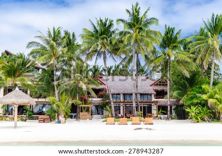 Luxury tropical villa near the sea with beautiful colourful decor, surrounding palm trees and lounges in front of it at famous exotic white sandy beach on Boracay island, station 1, Philippines  - stock photo