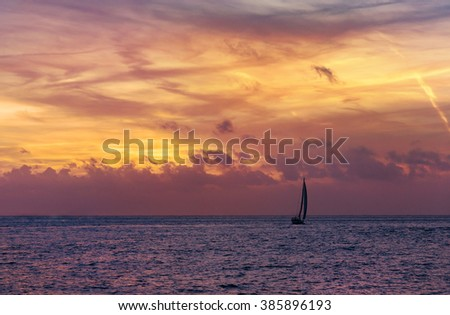 Luxury vacation concept - small sailboat on blue and purple water with magical red and yellow sunset clouds over horizon. - stock photo