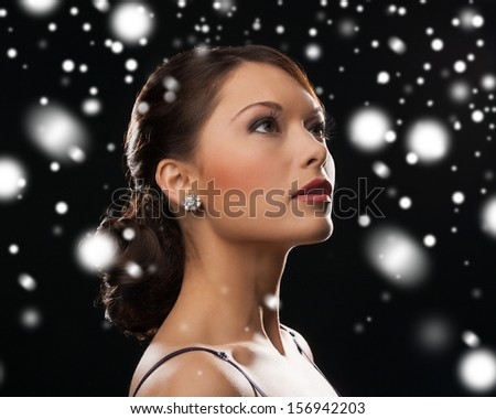 luxury, vip, nightlife, party, christmas, x-mas, new year's eve concept - beautiful woman in evening dress wearing diamond earrings - stock photo