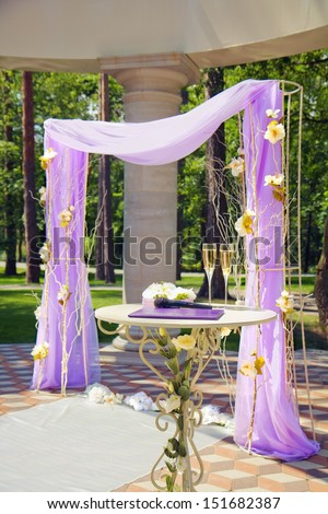 Luxury wedding gazebo with flower arrangements in summer park - stock photo