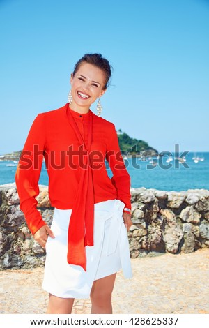Luxury weekend retreat. Happy young woman in bright blouse standing in front of the beautiful scenery overlooking lagoon with yachts - stock photo