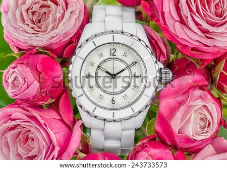 Luxury white woman watch on pink roses back ground - stock photo