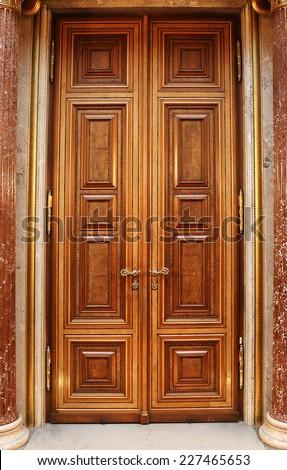luxury wooden door with golden ornaments. - stock photo