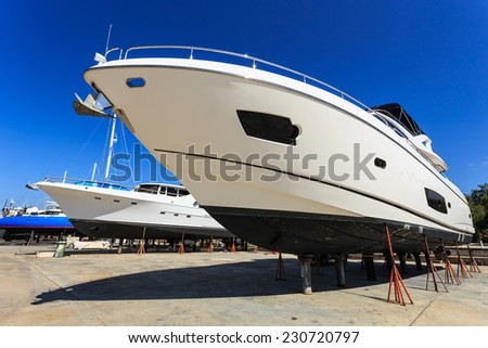 Luxury yacht beached for annual service and repair - stock photo
