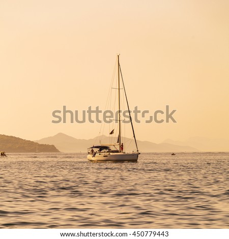 Luxury yacht sails on the Adriatic Sea coastline. Traveling near the island. The boat is sailing into the port at sunset. Dubrovnik, Croatia - stock photo