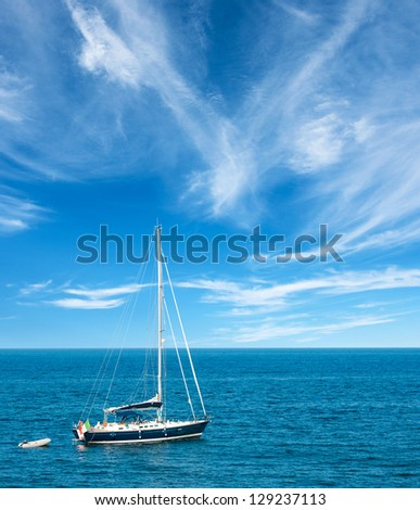Luxury yatch in open waters with beautiful clouds - stock photo