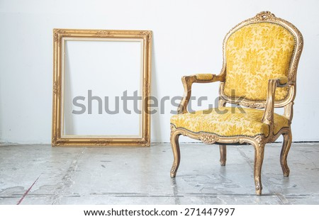 Luxury yellow vintage style armchair sofa with frame in a vintage room - stock photo