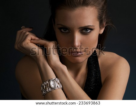 luxury young dark-haired girl in exclusive jewelry wrist watch poses in studio  - stock photo