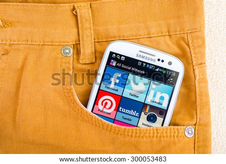 LVIV, UKRAINE - Jun 21, 2015: White Samsung Smart Phone with   social media applications  on screen in the pocket of orange jeans - stock photo