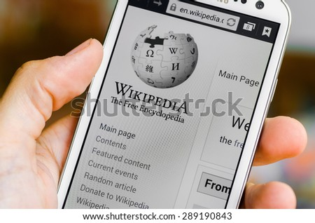 LVIV, UKRAINE - May 19, 2015: Hand holding white Samsung Smart Phone with Wikipedia main page screen - stock photo