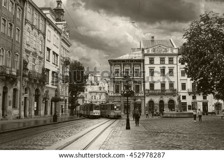 LVIV, UKRAINE - MAY 8, 2016:  The center of Lviv - The Market Square. Two trams passing along the street. Black and white photo. Ukraine - stock photo
