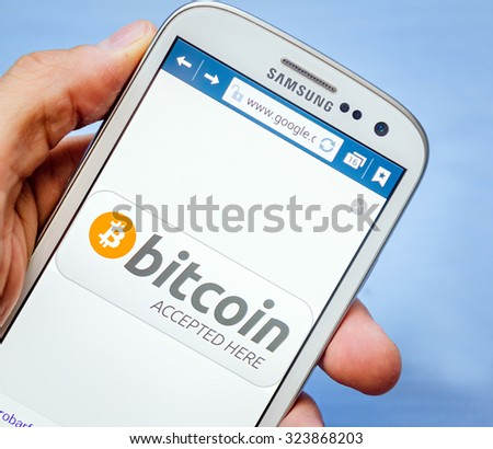 LVIV, UKRAINE - Sept 30, 2015: white Samsung Smart Phone with  bitcoin accept image on screen,  in hand - stock photo