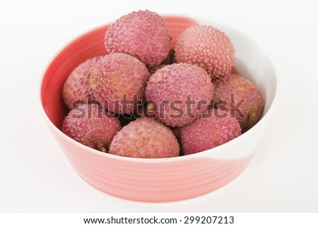 Lychees - Fresh lychees in a pink bowl. - stock photo