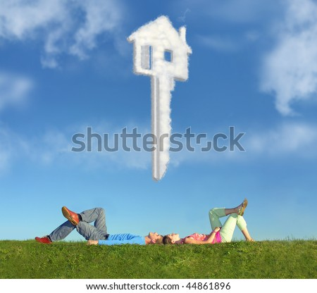 lying couple on grass and dream house key collage - stock photo