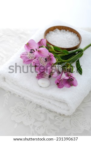 Lying down orchid with salt in bowl on towel with white stones and white lace  - stock photo