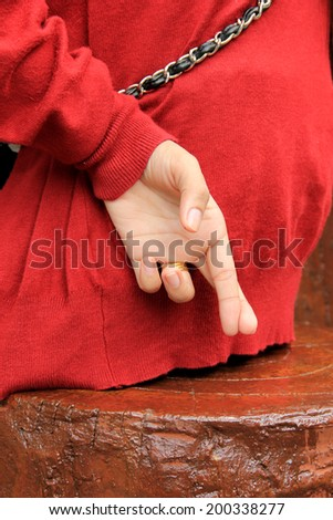 lying fake hand Fingers Crossed - stock photo
