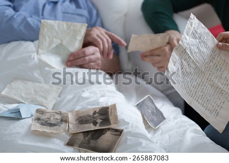 Lying in bed and looking at old photos - stock photo