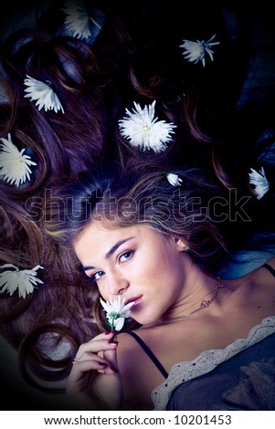 Lying young beautiful woman with flowers in her long hair - stock photo