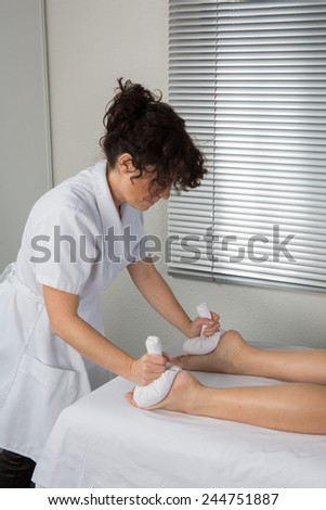 Lymphatic drainage massage therapist on woman leg with herbal bag - stock photo