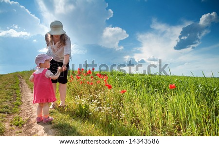 Ma with daughter amongst poppy-field - stock photo