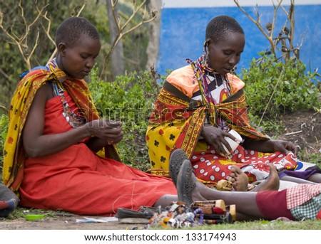 MAASAI MARA, KENYA-DECEMBER 27: Maasai women make traditional necklace 27 December, 2012 at Maasai Mara, Kenya. The Maasai are the most famous tribe in Africa. - stock photo