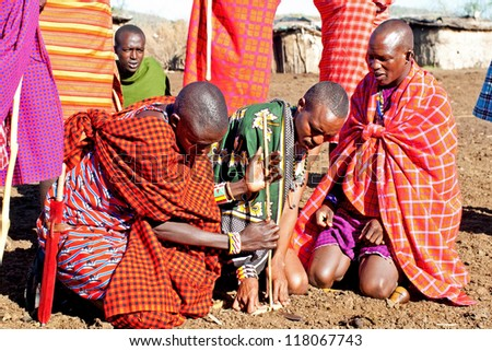 MAASAI MARA, KENYA-OCT 15: Group of unidentified Maasai men on Oct 15, 2012 in Maasai Mara, Kenya. Maasai are a Nilotic ethnic group of semi-nomadic people located in Kenya and northern Tanzania. - stock photo