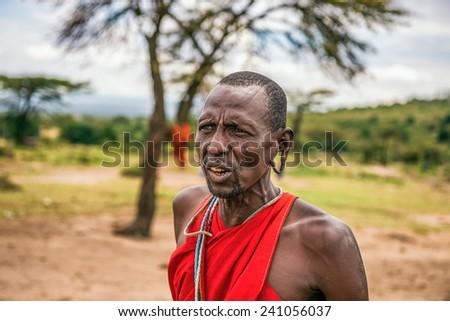 MAASAI MARA, KENYA - OCTOBER 17, 2014 : Portrait of an african men posing in his Masai tribe village. The Maasai are a Nilotic ethnic group living in southern Kenya and northern Tanzania - stock photo