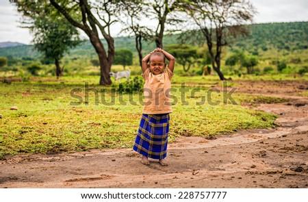MAASAI MARA, KENYA - OCTOBER 17, 2014 : Young african girl posing in a Masai tribe village. The Maasai are a Nilotic ethnic group living in southern Kenya and northern Tanzania - stock photo