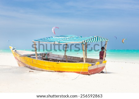 Maasai warrior lounging aroundon traditional colorful wooden boat on picture perfect tropical sandy beach on Zanzibar, Tanzania, East Africa. Kiteboarding spot on Paje beach. - stock photo