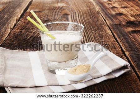 Maca powder on spoon and maca powder in milkshake on cloth on brown wooden table. Healthy living, alternative medicin, rustic styles.  - stock photo