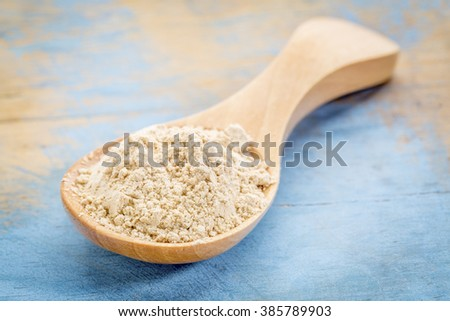 maca root  powder on wooden spoon against blue painted grunge wood - stock photo