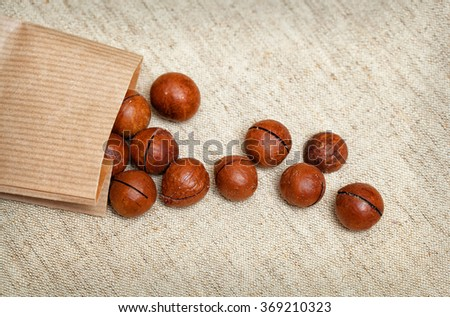 macadamia nuts spill out of the bag - stock photo