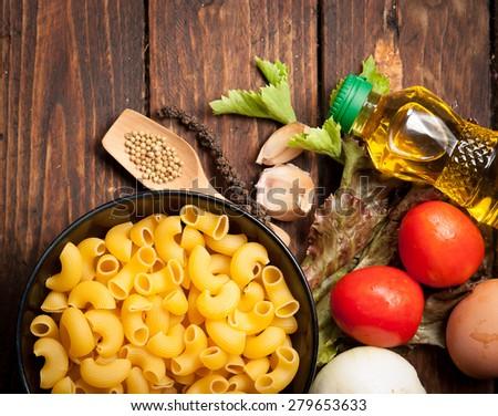 macaroni pasta spaghetti, vegetables and spices on wood - stock photo